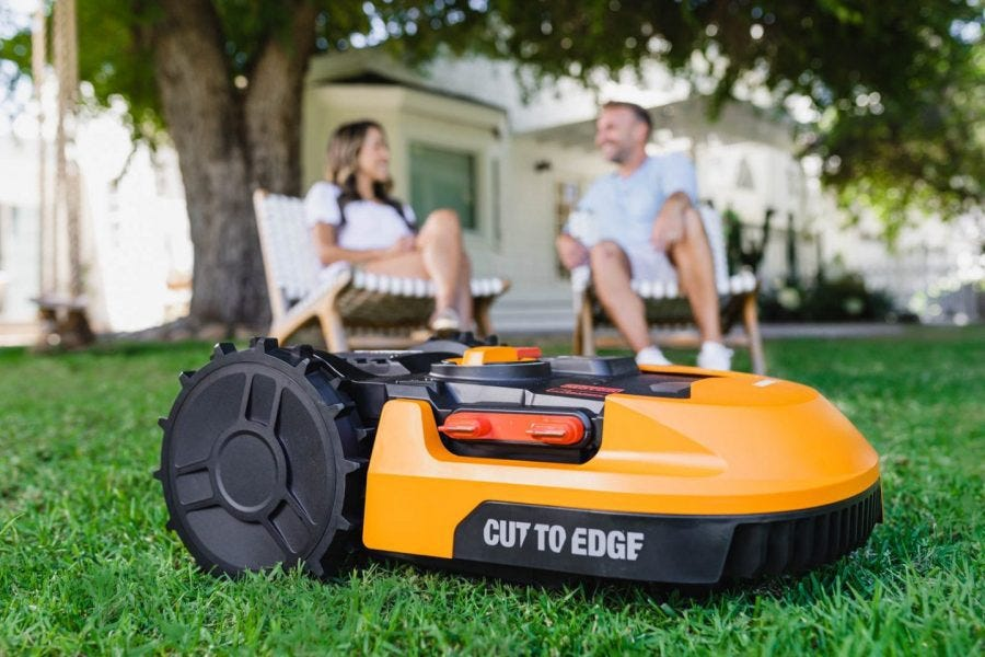 close up of Worx Landroid robotic lawn mower mowing lawn with man and woman sitting in the background