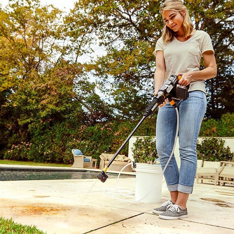 woman using worx hydroshot power cleaner to clean pool deck