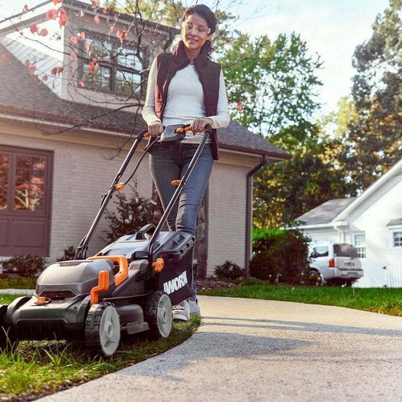 woman mowing edge of lawn using lawn mower with sharp blades