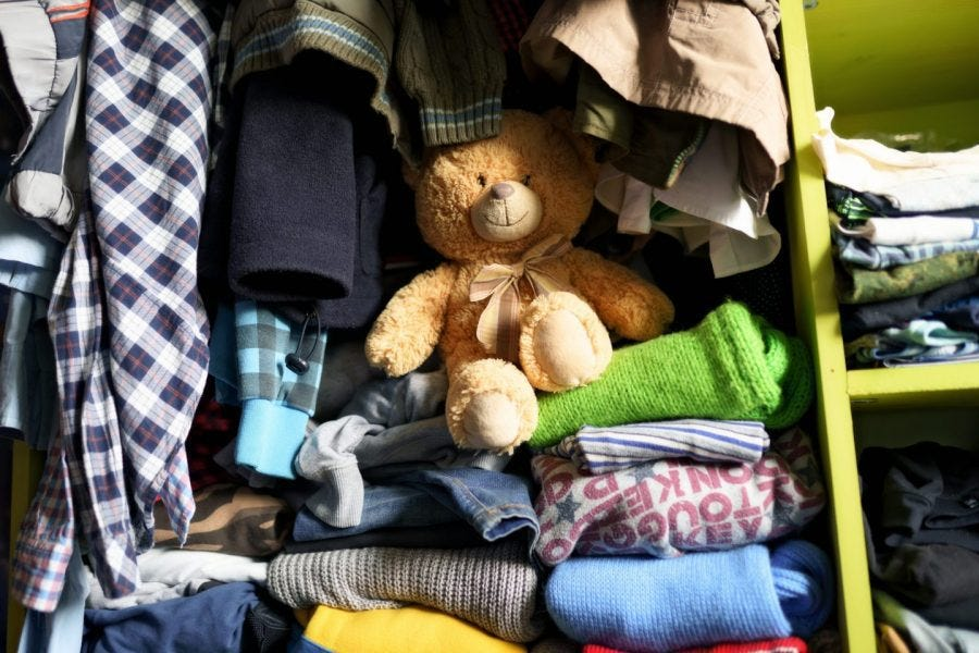 clothes and teddy bear stored inside closet cubby