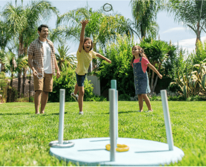 father and two daughters playing ring toss game with homemade game set